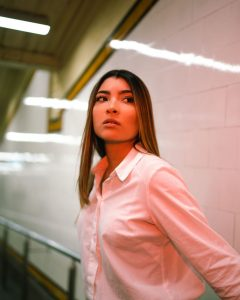 Photo of a person from the waist up, standing in a corridor and looking at something beyond the frame. They are lit by fluorescent lights that are partially visible.
